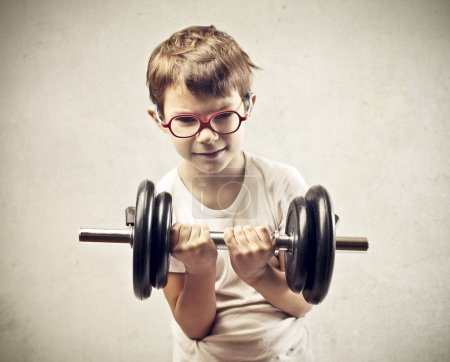 Photo for Child raising a dumbbell - Royalty Free Image