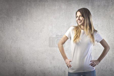 Photo pour Jeune femme heureuse avec un t-shirt blanc sur fond gris - image libre de droit