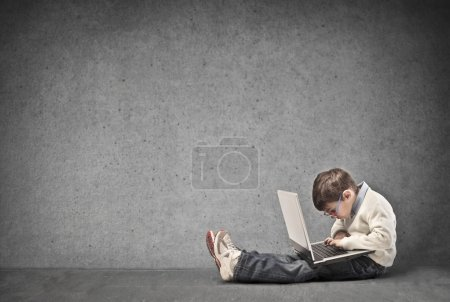 Photo for Small child sitting on the floor with laptop on his knees writes - Royalty Free Image
