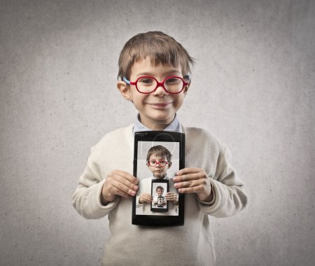 Child shows a tablet with portrait photographs repeated on a gray background
