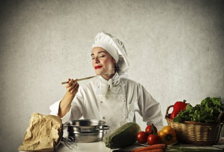 Photo for Beautiful chef who tastes a dish on a gray background - Royalty Free Image