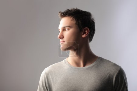Photo for Handsome man in profile on gray background - Royalty Free Image