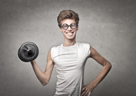 Photo for Nerdy guy with glasses and gym gear on gray background - Royalty Free Image