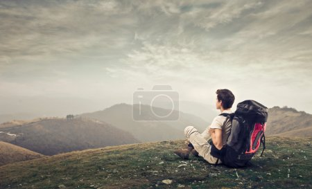 Photo for Boy with bag on his back sitting on grass in the mountains - Royalty Free Image
