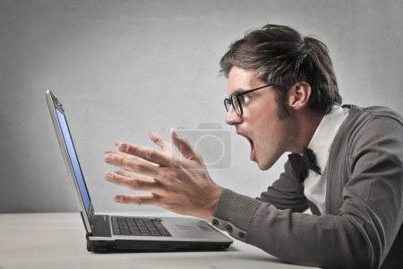 Photo pour Homme d'affaires à la recherche avec grande stupeur son ordinateur portable sur fond gris - image libre de droit