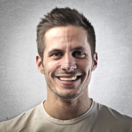 Portrait of handsome man smiling on gray background