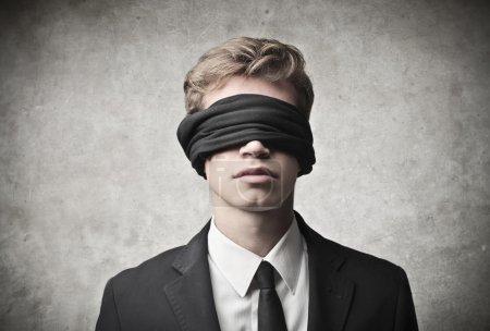 Photo pour Jeune homme d'affaires les yeux bandés sur fond gris - image libre de droit
