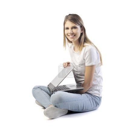 Foto de Chica rubia sentada en el suelo con portátil - Imagen libre de derechos