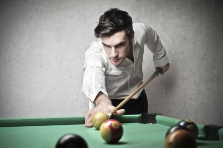 Handsome young man playing pool...