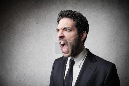 Photo pour Jeune entrepreneur crier sur fond gris - image libre de droit