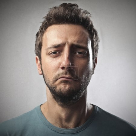 Photo for Portrait of sad young man on gray background - Royalty Free Image