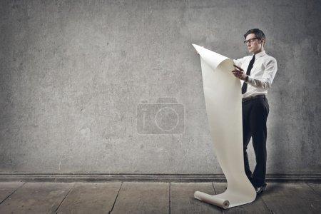 Photo pour Jeune homme d'affaires lit le projet - image libre de droit