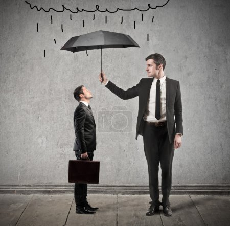 Photo for Businessman with umbrella protects young man - Royalty Free Image