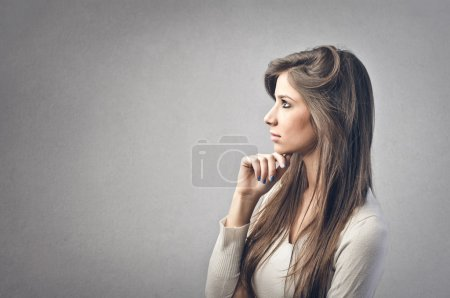 Photo for Profile of pretty young woman on gray background - Royalty Free Image