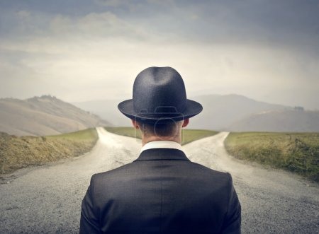 Photo for Elegant man with hat in front of a desert road - Royalty Free Image
