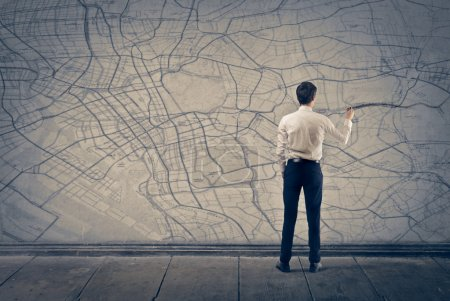 Photo for Young businessman writing on the map - Royalty Free Image
