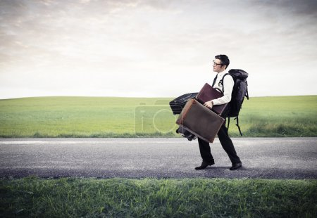 Photo for Young businessman on the road with many luggages - Royalty Free Image