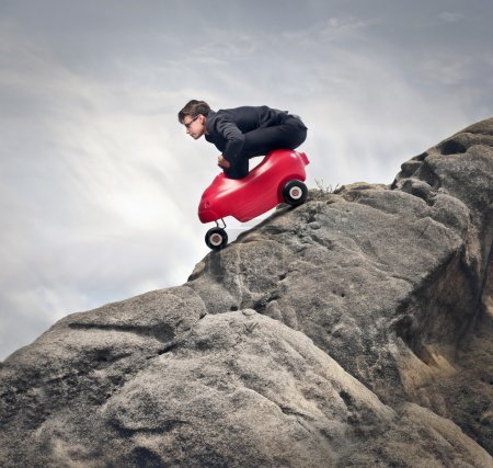 Photo for Young businessman on the rocks with red small car - Royalty Free Image