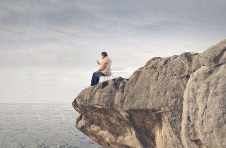 Photo pour Jeune grosse femme assise sur une falaise avec téléphone - image libre de droit