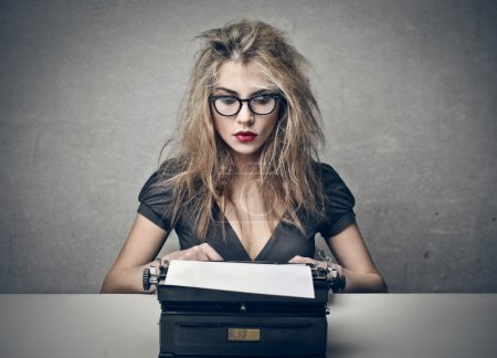 Photo pour Belle femme blonde écriture avec machine à écrire - image libre de droit