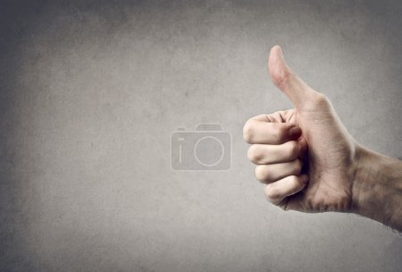 Photo for Hand with thumb upwards on a gray background - Royalty Free Image