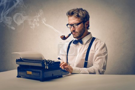 Photo for Young writer with typewriter and pipe - Royalty Free Image