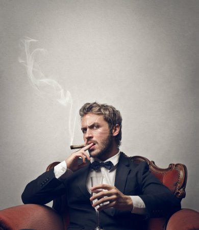 Boss smokes cigar with a glass of champagne...