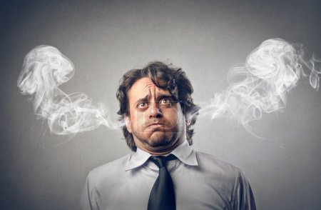 Stressful businessman with smoke coming out of his...