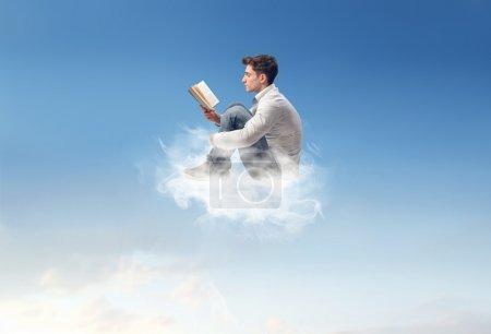 Photo pour Homme lisant sur un nuage - image libre de droit