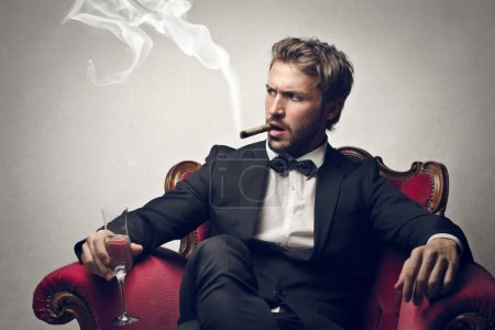 Photo for Boss sitting on a red armchair with cigar - Royalty Free Image