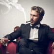 Boss sitting on a red armchair with cigar