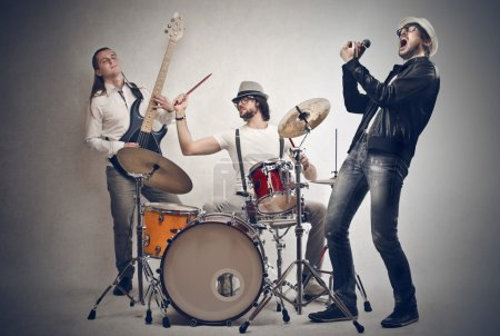 Photo for Men singing, playing the drums and the bass - Royalty Free Image