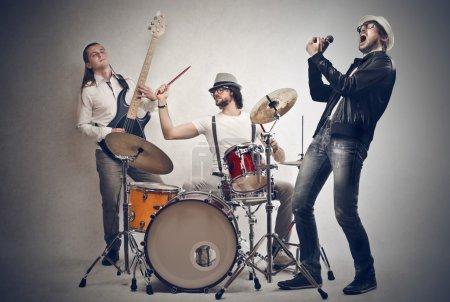 Photo pour Hommes chantant, jouant de la batterie et de la basse - image libre de droit