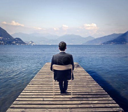Photo for Young businessman sitting on a chair relaxes at the lake - Royalty Free Image