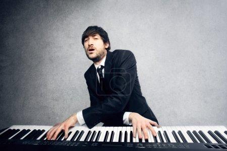 Photo pour Homme jouant du piano avec les bras croisés - image libre de droit