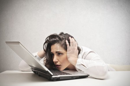 Photo for Desperate woman looking at her laptop - Royalty Free Image