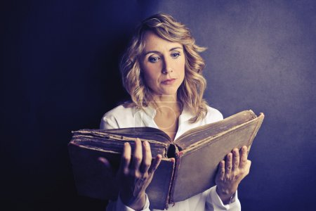 Photo for Concentrate woman reading an old book - Royalty Free Image