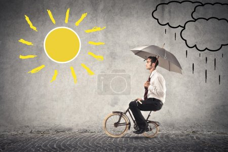 Photo for Businessman riding a small bike holding an umbrella - Royalty Free Image