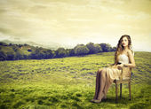 Beautiful woman sitting in the middle of as field