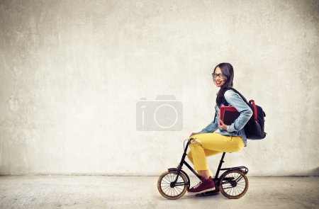 Beautiful girl student on a bike