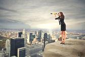 Business woman looking through a binoculars
