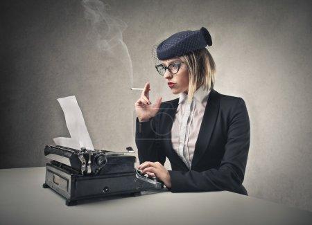 Photo pour Belle femme de mode tapant sur une machine à écrire et fumant - image libre de droit