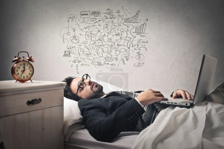 Photo for Businessman lying into bed working on his laptop and thinking hard - Royalty Free Image