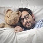 Man sleeping holding his teddy bear into bed