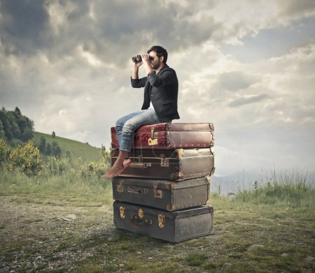 Photo for Man looking through a binoculars on some suitcases - Royalty Free Image
