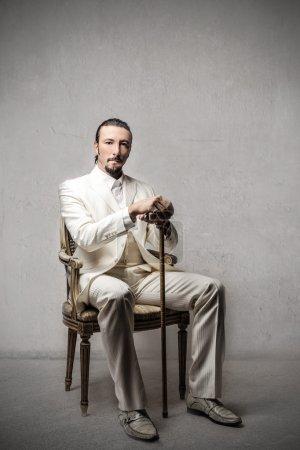 Photo pour Beau riche assis sur une chaise - image libre de droit