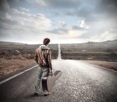 Photo pour Un homme tenant une guitare regardant la rue devant lui - image libre de droit