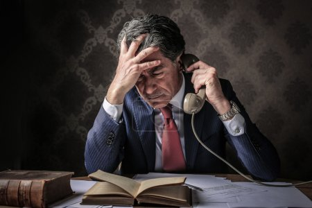 Photo for Desperate elegant man reading a book at the phone - Royalty Free Image