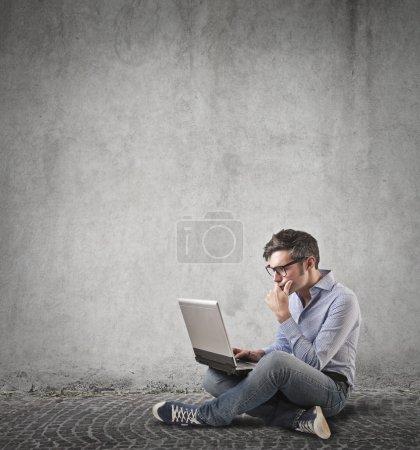 Photo pour Homme à la recherche et travaillant sur son ordinateur portable - image libre de droit