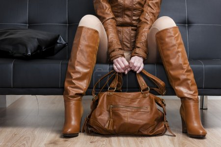 Woman wearing brown jacket and boots sitting on sofa